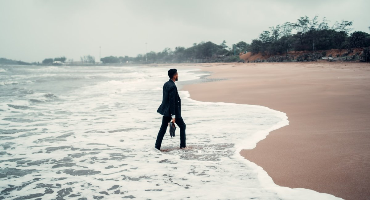 Man in business suit walking on a beach